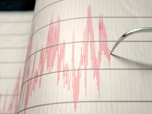 A closeup of a seismograph machine needle drawing a red line on graph paper depicting seismic and eartquake activity
